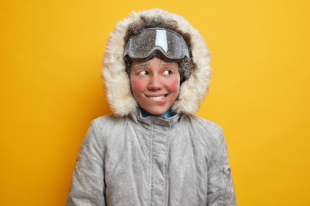 Portrait of cheerful frozen woman bites lips and looks away gladfully has adventure or winter expedition in tundra has hoarfrost face dresses for cold climate hiking in blizzard wears warm jacket