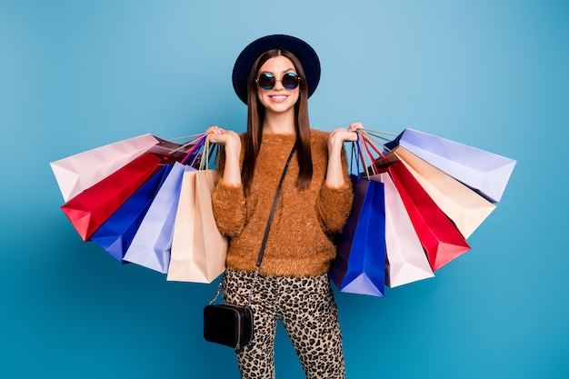 Portrait of cheerful funky girl tourist enjoy shopping weekends buy off-sales hold many bags wear velvet vintage hat clutch brown trousers pullover sunglass isolated blue color wall