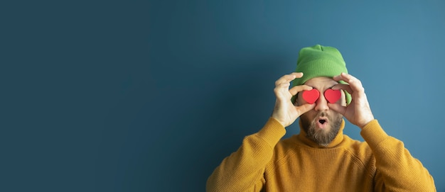 Portrait of a cheerful funny young hipster man with hearts in his eyes on a blue background.