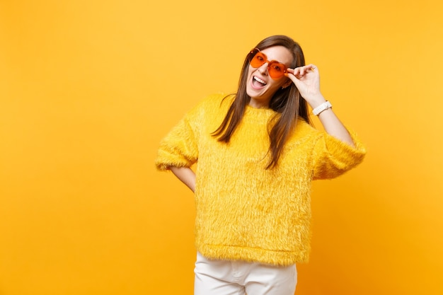 Portrait of cheerful funny young woman in fur sweater, white pants holding heart orange eyeglasses isolated on bright yellow background. people sincere emotions, lifestyle concept. advertising area.