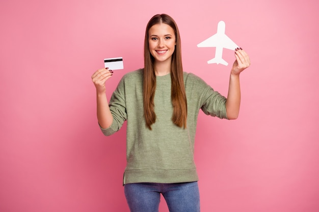Portrait of cheerful girl hold white paper card plane hold credit card