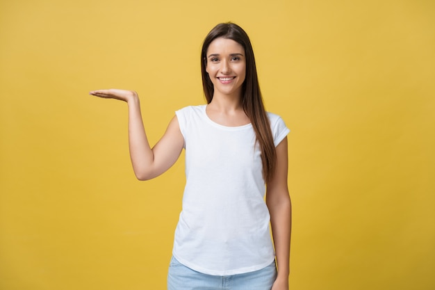 Portrait of a cheerful girl holding copyspace on the palm isolated on a yellow background.
