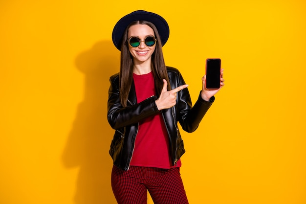 Portrait of cheerful girl recommending cellphone device direct finger