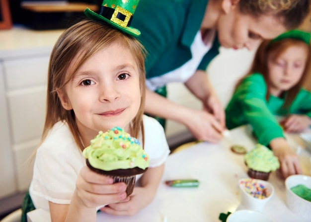 Portrait of cheerful girl showing cupcake
