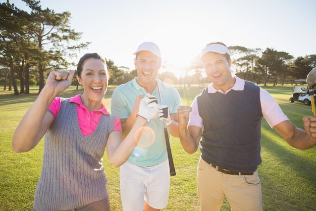 Portrait of cheerful golfer friends