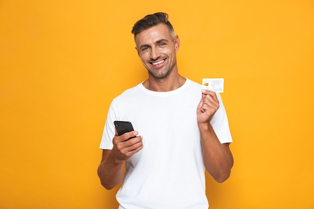 Portrait of cheerful guy 30s in white t-shirt holding mobile phone and credit card isolated on yellow