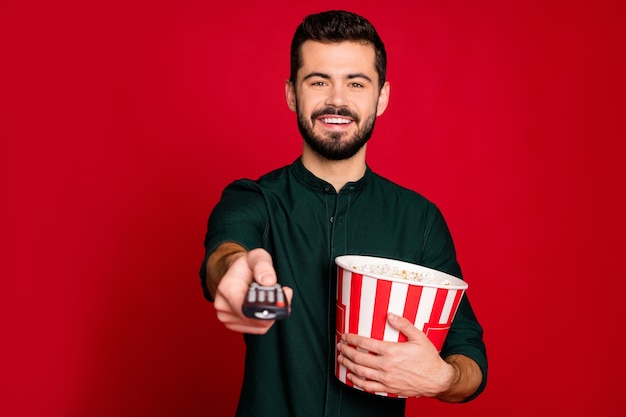 Portrait of cheerful guy have free time watch tv switch remote control hold big popcorn box enjoy emotion wear good looking outfit