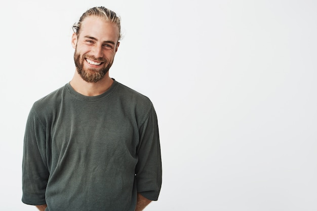 Portrait of cheerful handsome bearded guy with fashionable hairstyle smiling