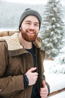 Portrait of cheerful handsome bearded young man standing in winter forest