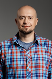 Portrait of cheerful handsome man in plaid shirt looking at camera smiling over grey wall
