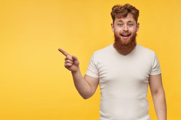 Ritratto di uomo bello allegro con barba e capelli rossi, indossa una maglietta vuota, indicando con un dito