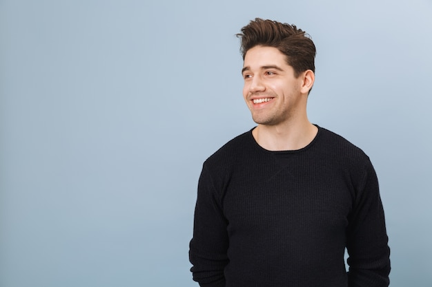 Portrait of a cheerful handsome young man standing isolated on blue, looking away
