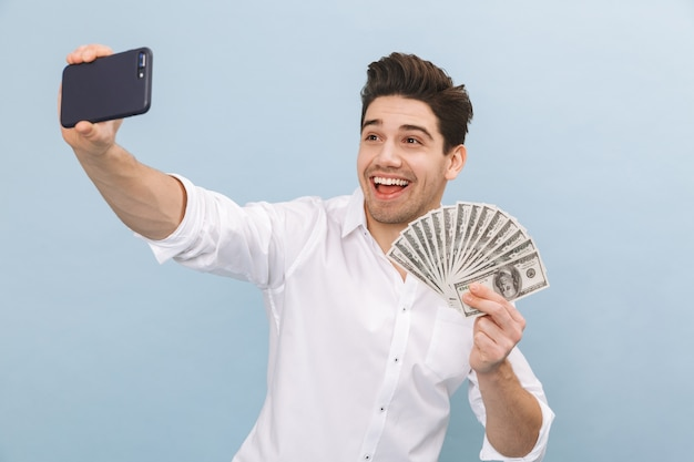 Portrait of a cheerful handsome young man standing isolated on blue, showing money banknotes, taking a selfie