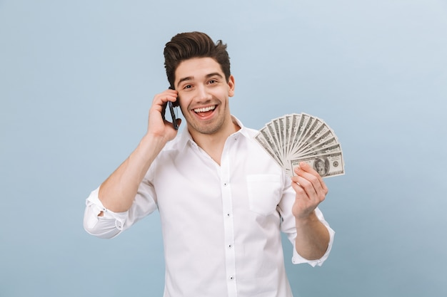 Portrait of a cheerful handsome young man standing isolated on blue, showing money banknotes, talking on mobile phone