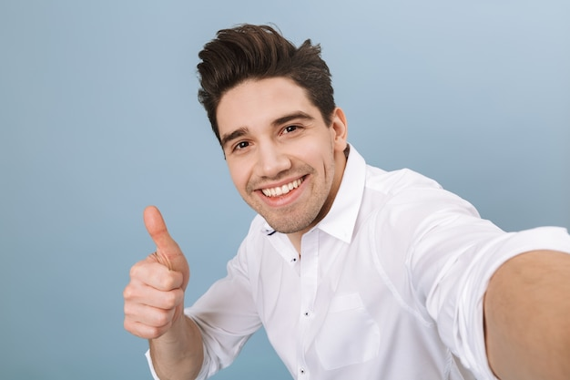 Portrait of a cheerful handsome young man standing isolated on blue, taking a selfie