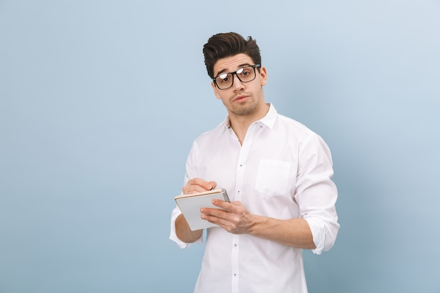 Portrait of a cheerful handsome young man wearing eyeglasses standing isolated on blue, taking notes