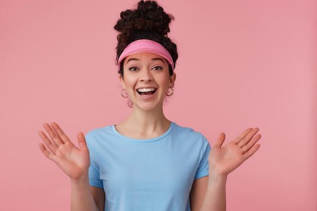 Ritratto di ragazza allegra e felice con chignon di capelli ricci scuri. indossa visiera rosa, orecchini e maglietta blu. ha il trucco. concetto di emozione