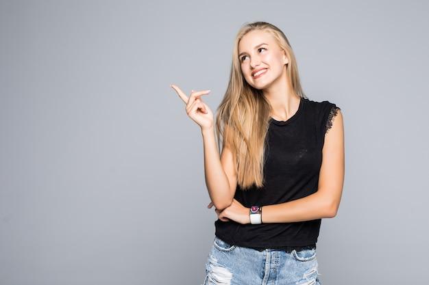 Ritratto di una giovane bella donna allegra e felice in una maglietta nera guardando con un sorriso la telecamera e puntando il dito sul lato isolato su sfondo grigio.