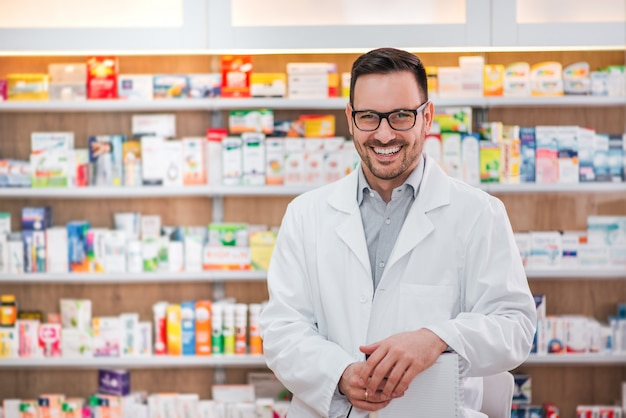 Portrait of a cheerful healthcare worker in white coat at pharmaceutical store.