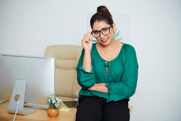 Portrait of cheerful indian busineswoman standing at her office desk, touching glasses and smiling at camera