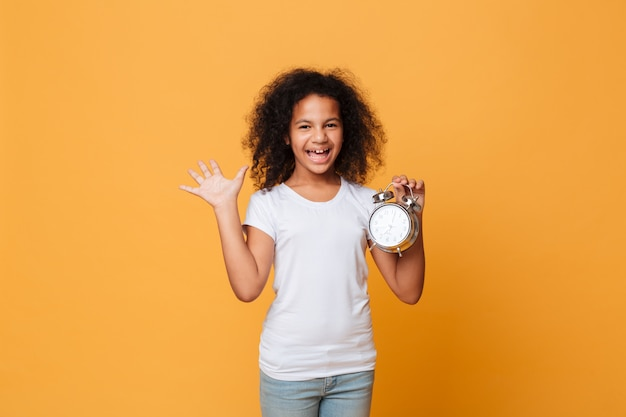 Portrait of a cheerful little african girl holding alarm clock