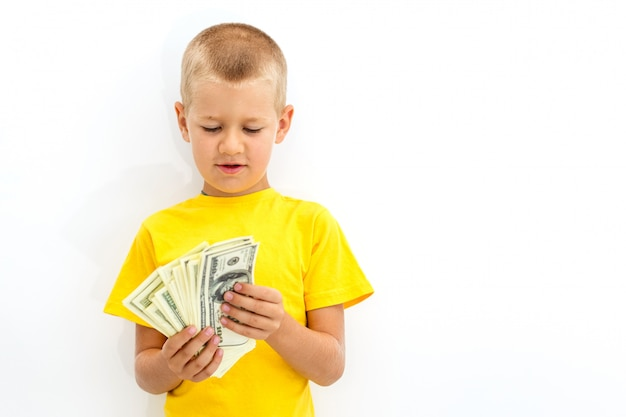 Portrait of a cheerful little boy holdg a dollars over white