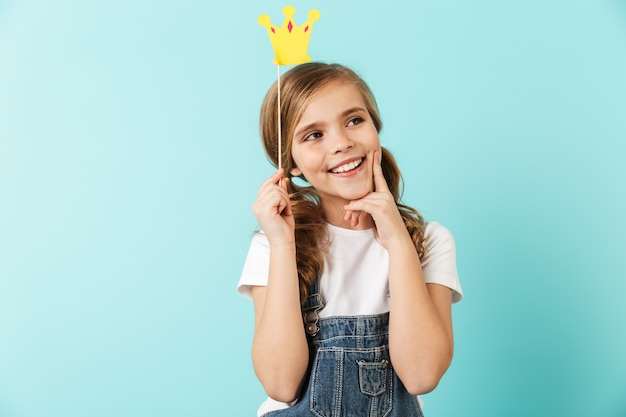 Portrait of a cheerful little girl isolated over blue wall, wearing little crown