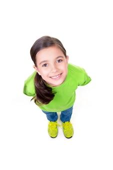 Ritratto della bambina allegra che osserva in su in maglietta verde. vista dall'alto. isolato su sfondo bianco.