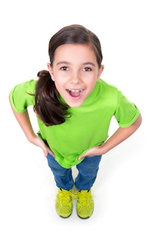 Portrait of cheerful little girl looking up in green t-shirt. top view. isolated on white wall.