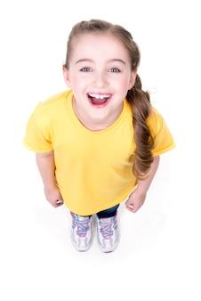 Ritratto della bambina allegra che osserva in su in maglietta gialla. vista dall'alto. isolato su sfondo bianco.