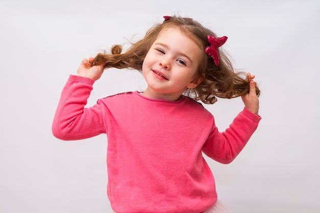 A portrait of a cheerful little girl playing with her hair