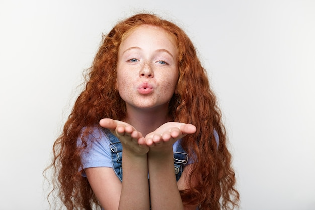 Portrait of cheerful little girl with ginger hair and freckles, send kiss at the cam, looks happy, standing over white wall.