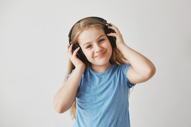 Portrait of cheerful little girl with light long hair and blue eyes in big earphones, listening to music with happy expression.