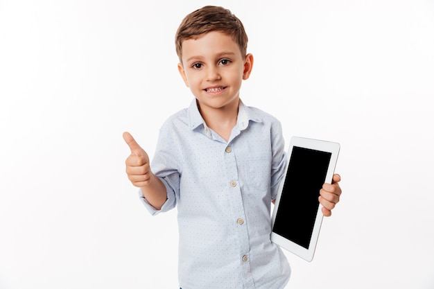 Portrait of a cheerful little kid holding blank screen tablet