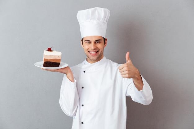 Il ritratto di uno chef maschio allegro si è vestito in uniforme