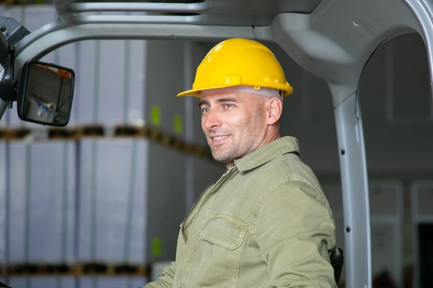 Portrait of cheerful male warehouse worker in hardhat sitting on forklift seat, smiling, looking away