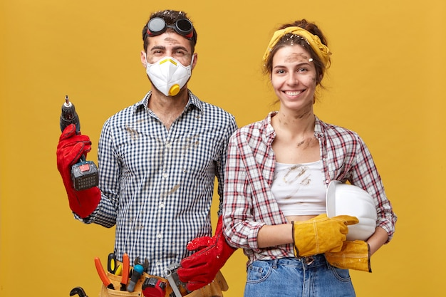 Portrait of cheerful male wearing protective mask, goggles and gloves holding drill fixing something at house and his wife who is helping him with construction holding hardhat. service workers