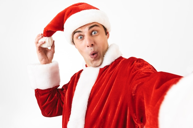Portrait of cheerful man 30s in santa claus costume and red hat laughing while taking selfie photo