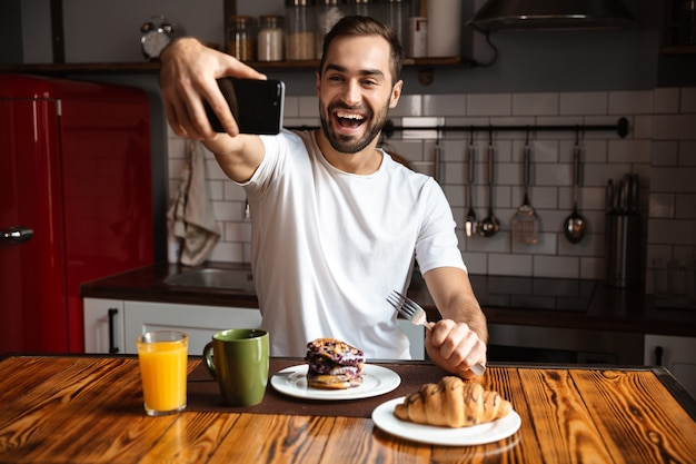 Portrait of cheerful man 30s taking selfie photo on mobile phone while having breakfast in stylish kitchen at home