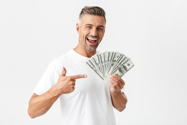 Portrait of cheerful man 30s wearing casual t-shirt smiling and holding bunch of money banknotes isolated on white