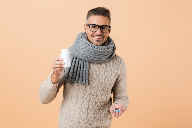 Portrait of a cheerful man dressed in sweater and scarf standing isolated over beige wall, showing pills capsules