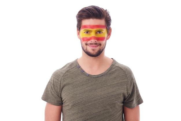 Ritratto di uomo allegro con bandiera spagnola sul viso