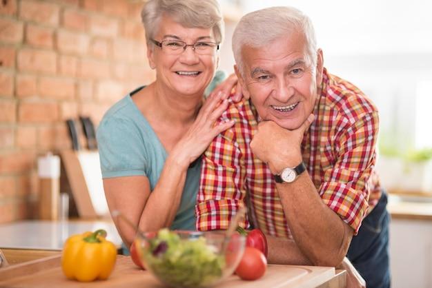 Ritratto di matrimonio allegro presso la cucina domestica