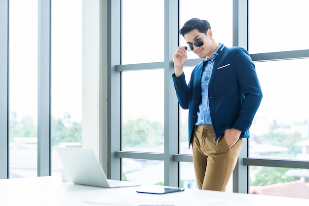 Portrait of a cheerful mature asian young businessman wear a business suit of man in blue jacket and blue shirt  touching his glasses at window in the office room .
