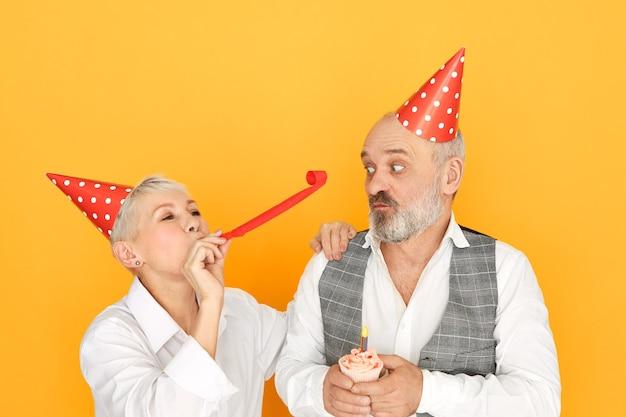 Ritratto di donna matura allegra che soffia tubo di carta mentre si diverte alla festa di compleanno in piedi accanto al suo anziano marito barbuto in cappello a cono