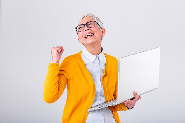 Portrait of a cheerful mature woman with a laptop computer and celebrating success isolated over gray background.