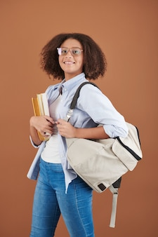 Portrait of cheerful mixed-race high school girl with afro hairstyle standing with modern satchel and books
