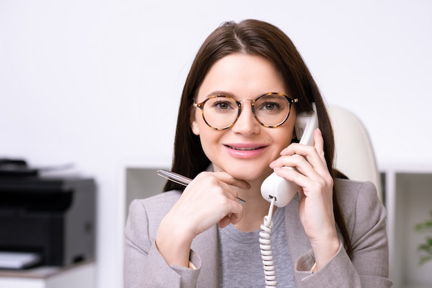 Portrait of cheerful modern lady in glasses holding pen and answering phone call while working in office