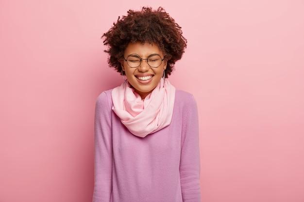 Ritratto di giovane donna allegra felicissima con un sorriso a trentadue denti, tiene gli occhi chiusi, ride di qualcosa di divertente, ha un umore perfetto, mostra i denti bianchi, indossa maglione e sciarpa casual, modelli indoor.