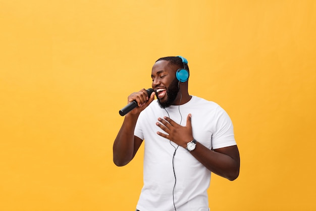 Portrait of cheerful positive chic handsome african man holding microphone and having headphones